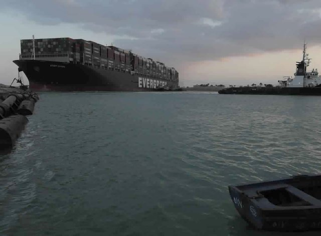 Ttug boats work to free the Panama-flagged, Japanese-owned Ever Given, which is lodged across the Suez Canal