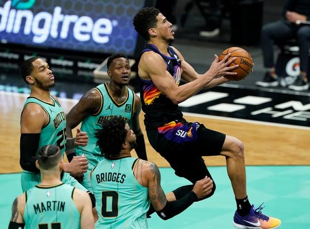 Phoenix Suns guard Devin Booker scores past the Charlotte Hornets