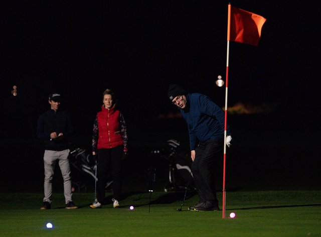 Golfers use neon coloured balls under floodlights at Morley Hayes Golf centre