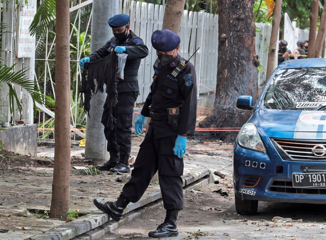A member of the police bomb squad, left, holds a piece of cloth found at the site of Sunday's suicide bomb attack at the Sacred Heart of Jesus Cathedral in Makassar, South Sulawesi, Indonesia (Yusuf Wahil/AP)
