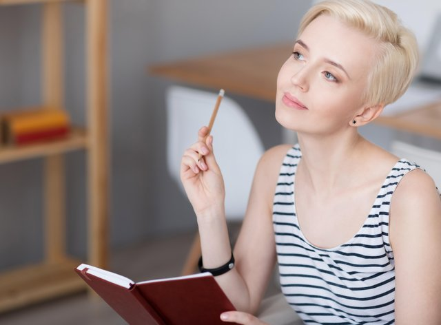 Woman thinking and holding diary