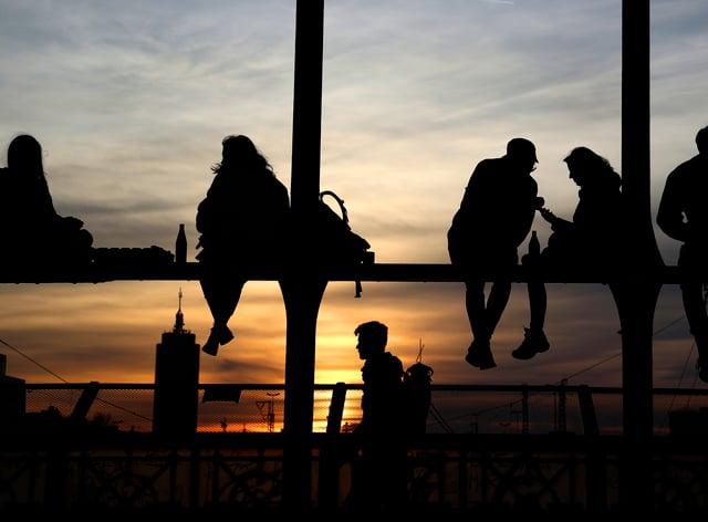 Young people enjoy the sunset at the bridge 'Hackerbruecke' in Munich, Germany (Matthias Schrader/AP)