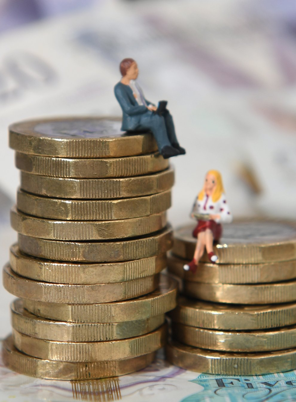 Models of a man and woman on unequal piles of coins