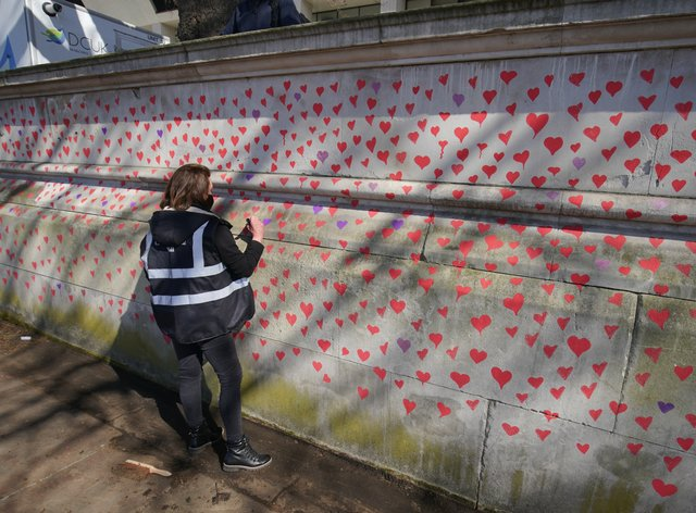 A woman paints red hearts on the Covid-19 memorial wall opposite the Houses of Parliament in central London (Aaron Chown/PA)