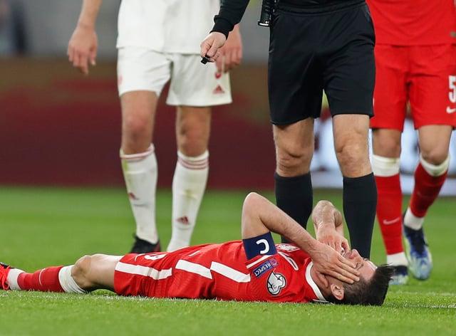 Robert Lewandowski lies on the pitch in Hungary