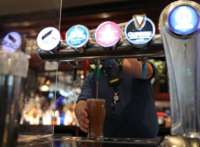 A member of bar staff pulls a pint at the Shakespeares Head pub in Holborn