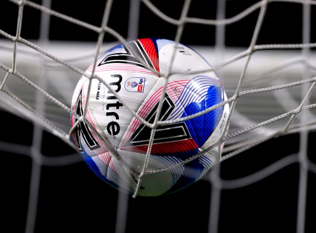 A football resting on the top of a net