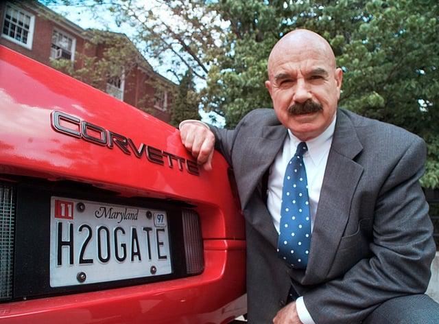 G Gordon Liddy kneels next to his Corvette in this 1997 photo