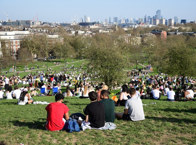 Groups of people sit in a park and enjoy the sunshine