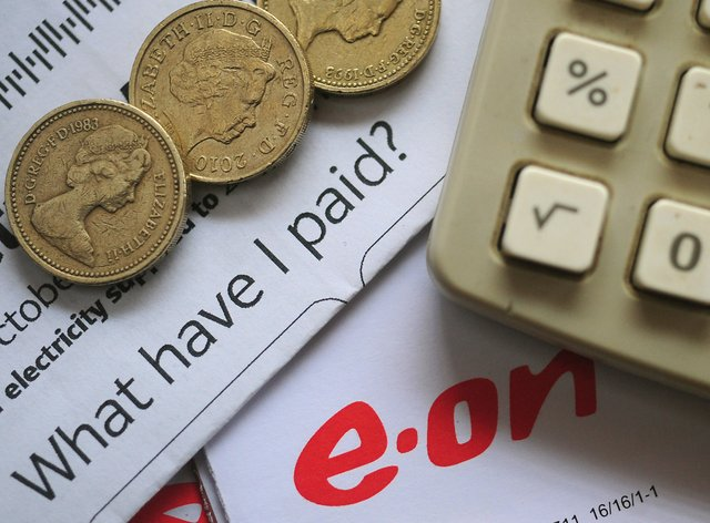 An EON energy bill with pound coins and a calculator