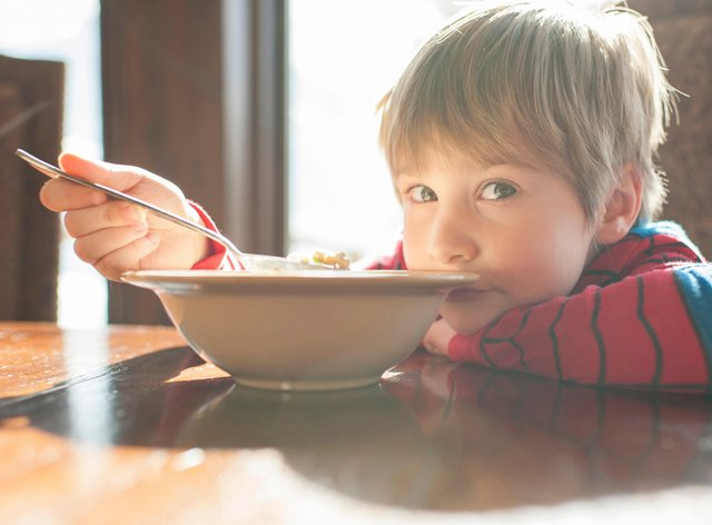Portrait of boy eating food while leaning on table at home