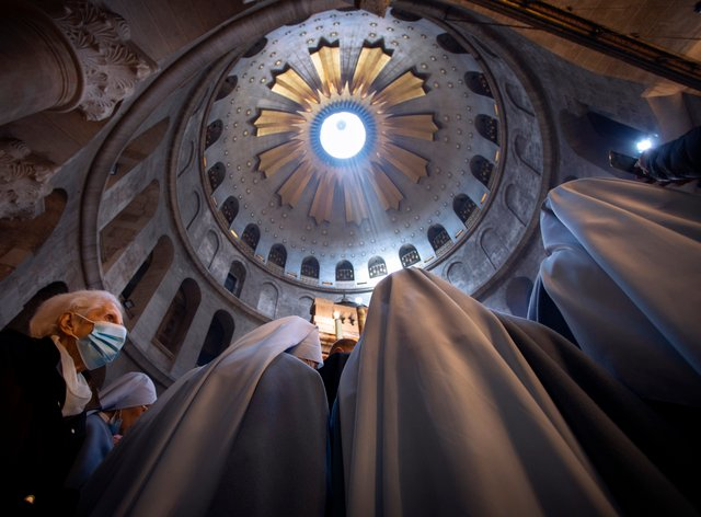 A woman wearing a face mask attends Easter Sunday mass led by Latin Patriarch of Jerusalem Pierbattista Pizzaballa at the Church of the Holy Sepulchre, where Jesus Christ is believed to have been buried, in the Old City of Jerusalem (Oded Balilty/AP)
