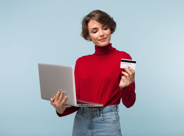 Woman with laptop and credit card, thinking carefully