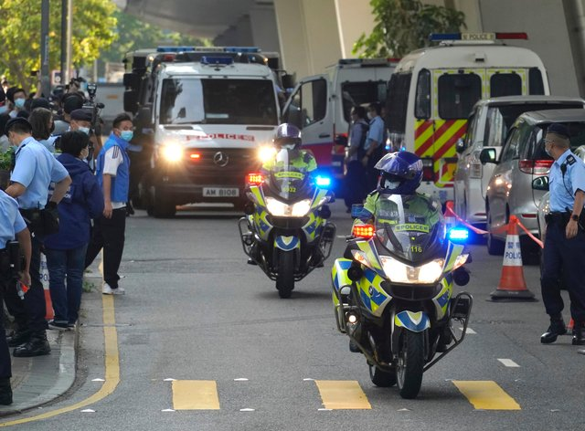 Police officers escort a prison van carrying Hong Kong pro-democracy activist Andy Li as it is leaving court in Hong Kong (Kin Cheung/AP)