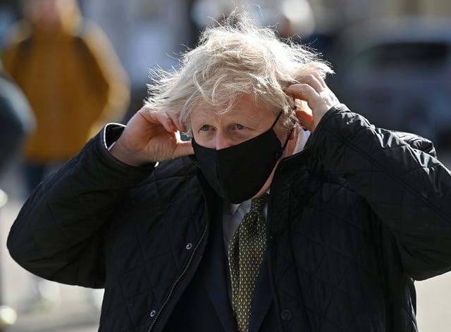Prime Minister Boris Johnson puts on a mask