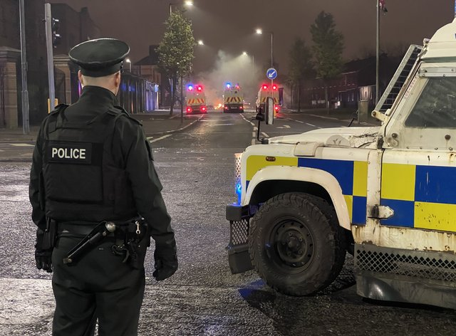 A PSNI officer stands on North Queen Street in Belfast looking towards Tigers Bay