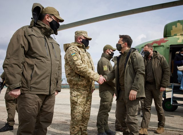 Ukrainian President Volodymyr Zelenskiy shakes hands with a soldier as he visits the war-hit Donetsk region (AP)