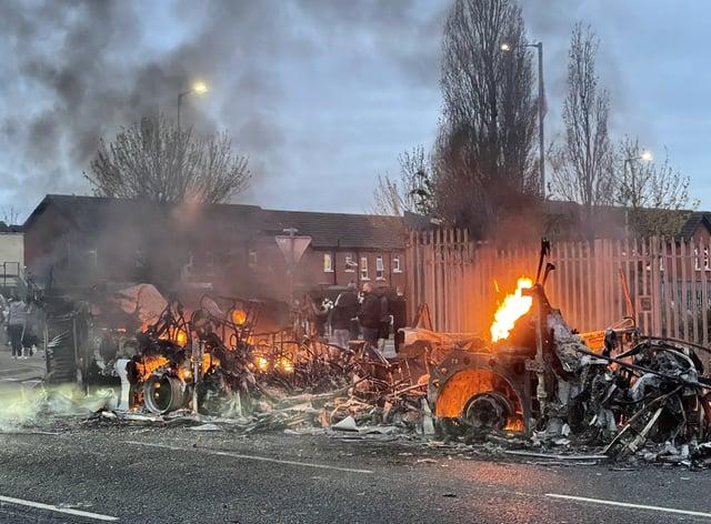 The wreckage of a Translink Metrobus on fire on the Shankill Road in Belfast