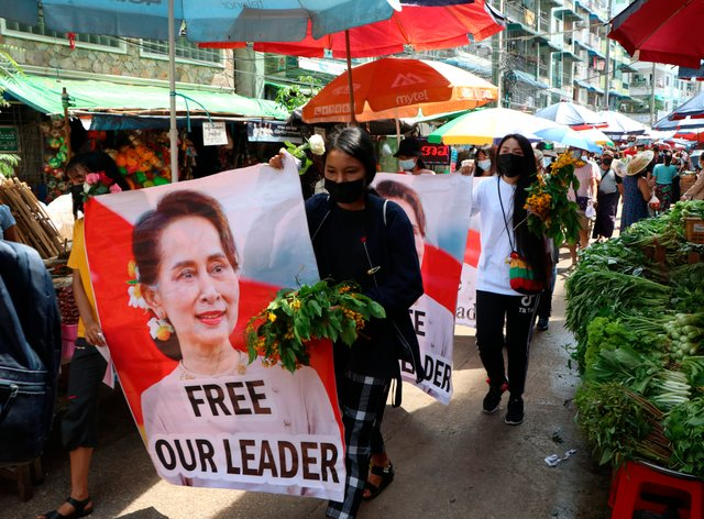 Protesters walk through Myanmar, Yangon, with a banner of Aung San Suu Kyi