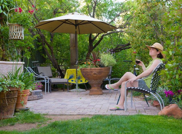 Woman relaxing in the garden with glass of wine