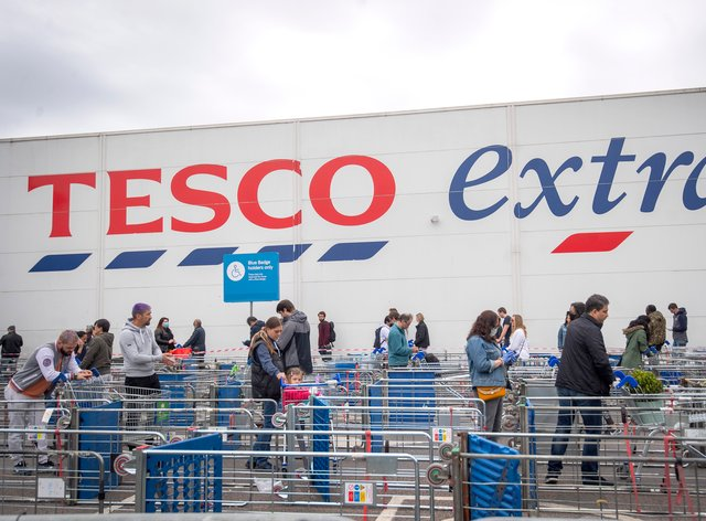 Customers queue outside a Tesco Extra store