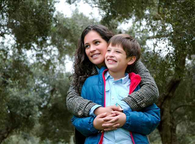 Woman with her arms around her son, out in nature