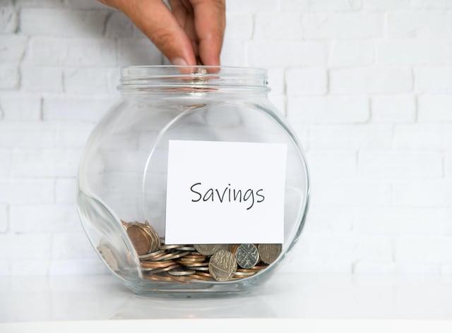 UK Money Jar on a white shelf in a household living room.
