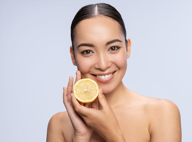 woman holding a cut lemon