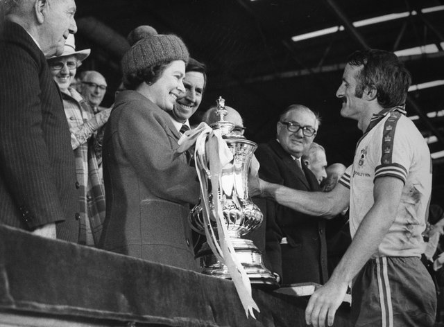 The Queen presents Southampton captain Peter Rodrigues with the FA Cup after the 1976 final at Wembley.