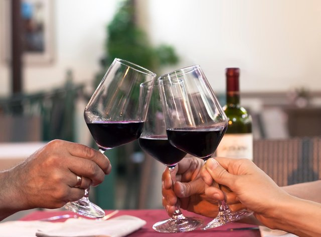 Friends clinking glasses of red wine outdoors