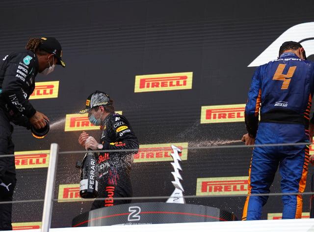Lewis Hamilton, left, sprays race winner Max Verstappen with champagne on the podium