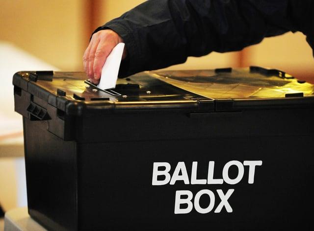 A voter placing a ballot paper in a ballot box