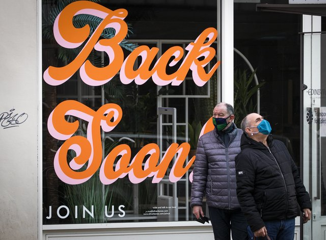 Sign that reads 'Back Soon' in the window of a closed shop in Edinburgh