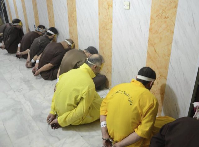 Blindfolded prisoners await their executions in Iraq
