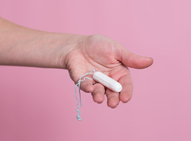 Woman's hand holding a clean cotton tampon