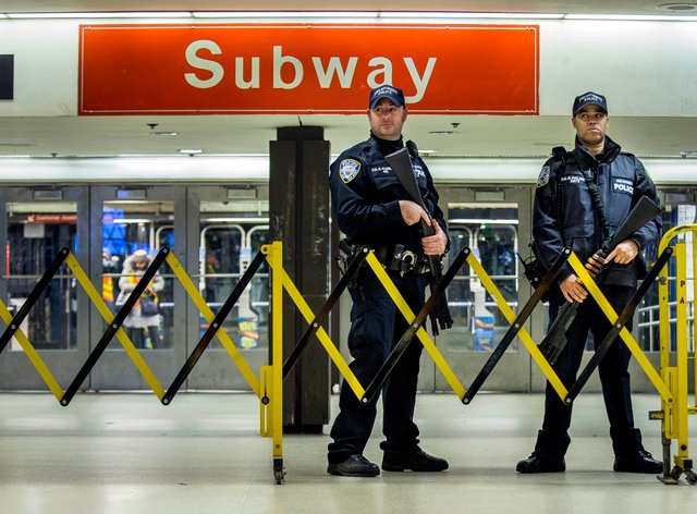 Police stand guard inside the Port Authority Bus Terminal following an explosion near Times Square in New York in 2017