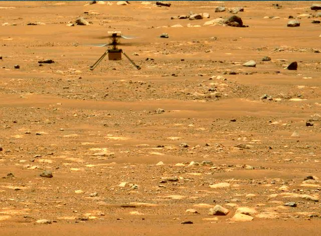The Mars Ingenuity helicopter hovers above the surface of the planet during its second flight