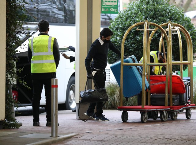Hotel staff load the luggage of passengers entering quarantine onto trolleys outside the Holiday Inn hotel, near Heathrow Airport
