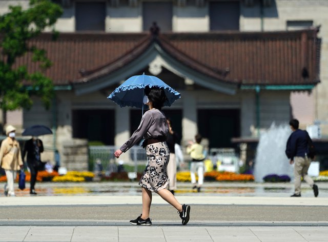 A woman wearing a protective mask to help curb the spread of the coronavirus walks at a park in Tokyo