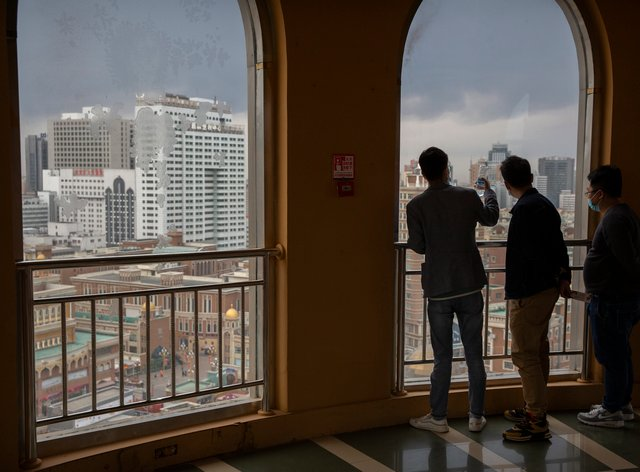 Visitors look at the Urumqi skyline from an observation tower at the International Grand Bazaar in Urumqi in western China's Xinjiang Uighur Autonomous Region (Mark Schiefelbein/AP)