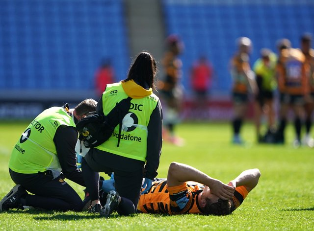 Joe Launchbury receives medical attention after taking a blow to his left knee