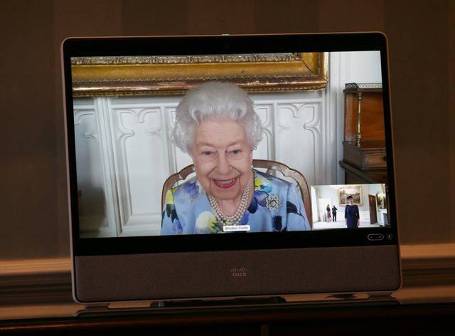 The Queen appears on a screen by videolink from Windsor Castle
