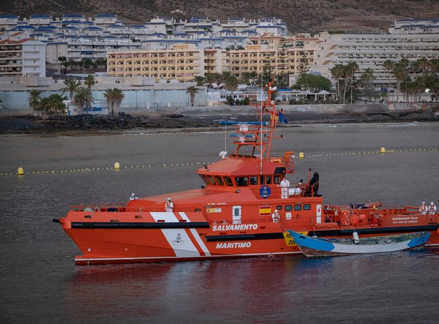 A wooden boat is towed by a Spanish Maritime Rescue Service ship