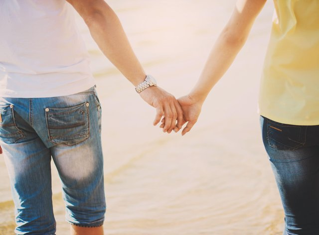 Couples holding hands. Summer in love. Close up of loving couple holding hands on a beach near the sea