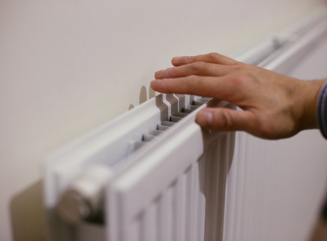 A person feels the warmth from a radiator at a home.