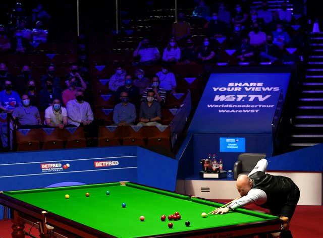 England's Stuart Bingham plays a shot watched by fans inside The Crucible