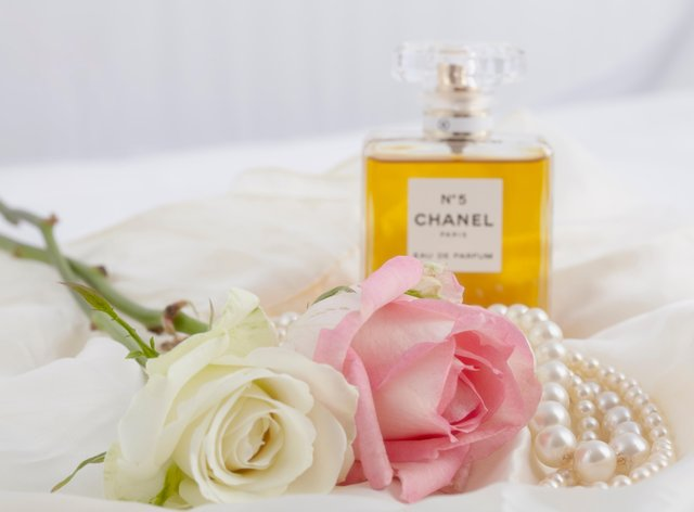 Chanel No5 bottle next to roses and pearls