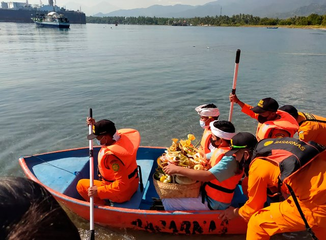 National Search and Rescue Agency personnel help relatives of Captain Gede Kartika, one of the junior officers of Indonesian Navy submarine KRI Nanggala that sank on April 21, to carry offerings to the sea during a prayer in Celukan Bawang, Bali (Al Rizki/AP)