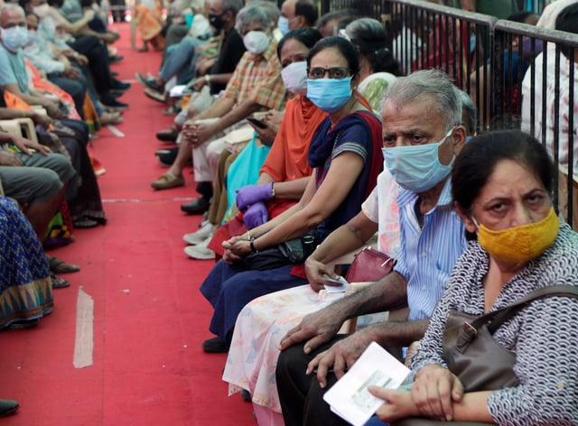 People wait to receive the Covid-19 vaccine in Mumbai, India (Rajanish Kakade/AP)