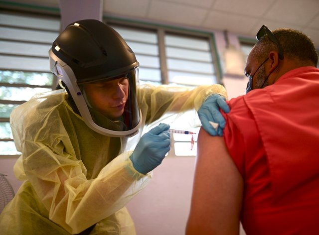 A healthcare worker injects a man with a dose of the Moderna Covid-19 vaccine in Puerto Rico